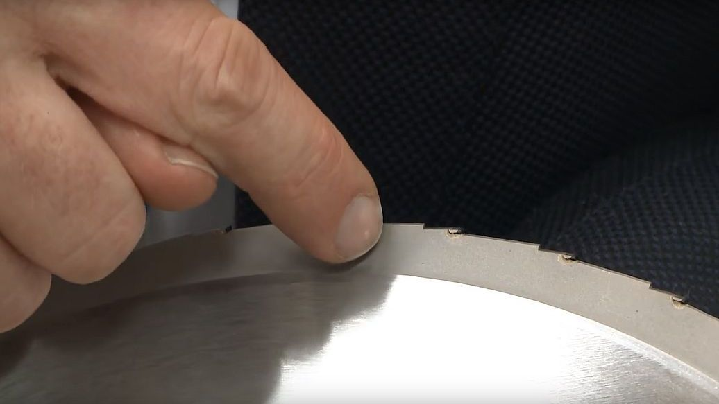 Finger points to saw teeth on a circular saw blade AKE Super Silent