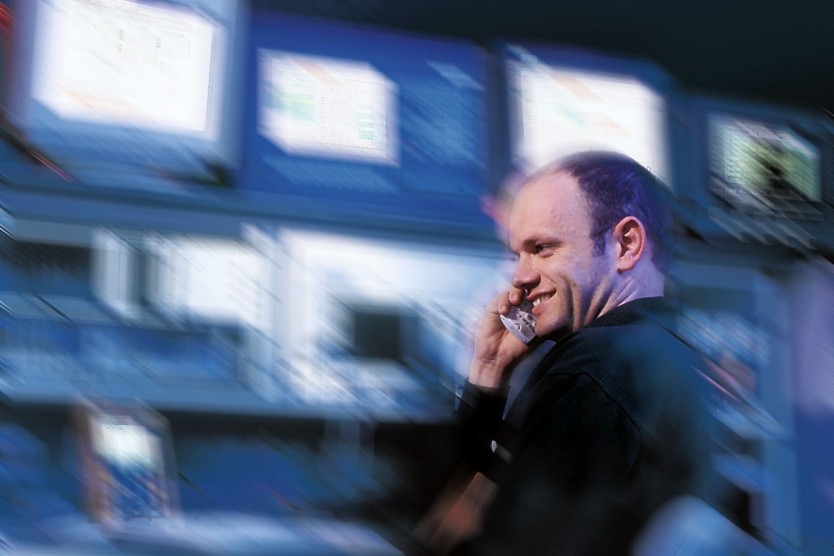 Telephoning man in front of a blurred background of monitors